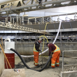 Two workers using Air-Vac hoses to excavate under concrete